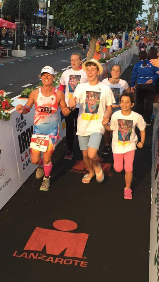 Triumphant and jubilant, Sandy is escorted to the finishing line by members of her family